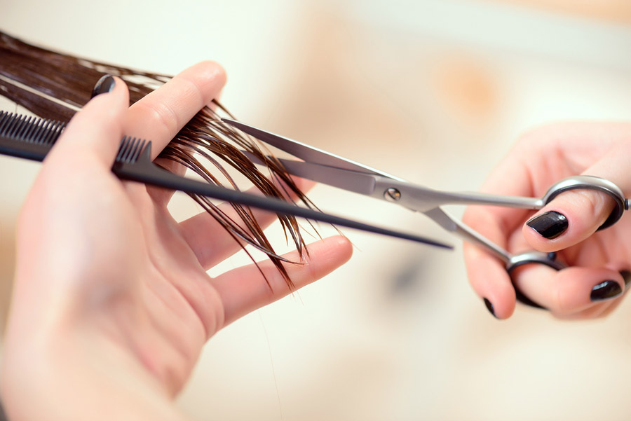 Getting rid of those split ends. Cropped shot of a female hairdresser cutting clients hair with scissors at beauty salon